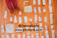 Photo of Pictues of a womans feet. She is standing amid piles of receipts. Home Financial Tax Planning.  Hardwood floor and bare feet.
